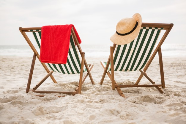 straw-hat-and-towel-kept-on-beach-chairs_1252-480
